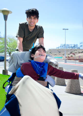 cerebral palsy: Teen boy pushing happy disabled biracial little  brother in wheelchair, smiling and laughing, outdoors. cerebral palsy Stock Photo