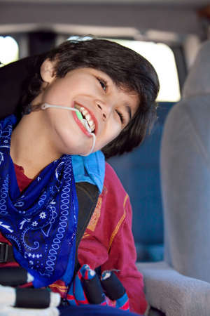 cerebral palsy: Disabled biracial eight year old boy sitting in carseat inside vehicle, smiling. Child has cerebral palsy.