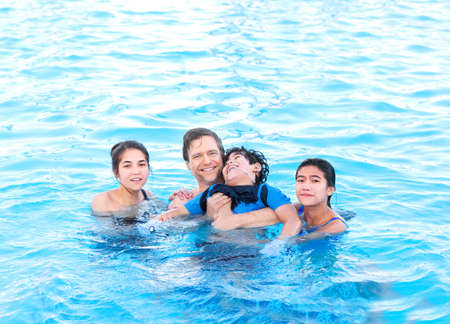 handicap: Multiracial family swimming together in pool. Disabled youngest son has cerebral palsy.