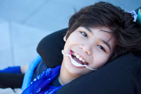 cerebral palsy: Handsome nine year old disabled boy in wheelchair smiling, looking up