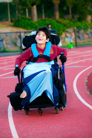 biracial: Young biracial disabled boy in wheelchair racing around the track