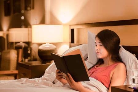 cama: Hermoso libro birracial asiático de la muchacha adolescente de raza caucásica la lectura en la cama por la noche con la luz de la lámpara de color amarillo en las paredes Foto de archivo