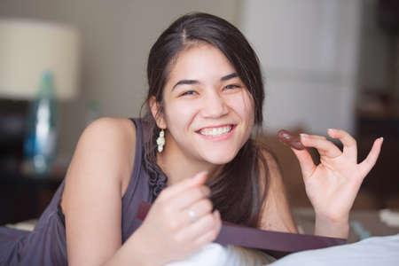 biracial: Beautiful biracial Asian Caucasian teen girl lying on bed holding chocolates, smiling