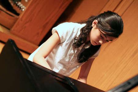 scandinavian girl: Young teen girl playing music on a grand piano Stock Photo