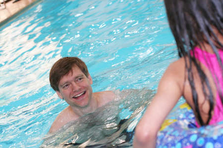 flotation: Father teaching his daughter to swim