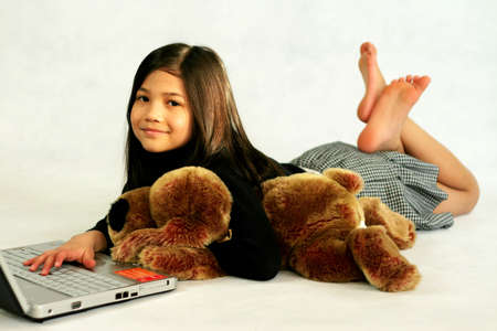 scandinavian girl: Happy child enjoying her  laptop while hugging her doll Stock Photo