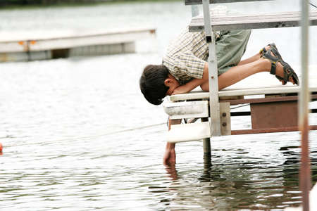 curiously: Young boy curiously putting his hand in water off of pier in summer