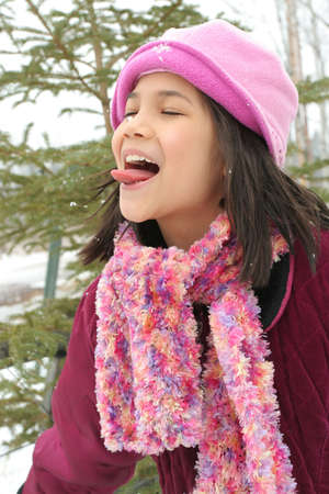 falling out: Nine year old girl sticking out her tongue trying to catch a snowflake Stock Photo