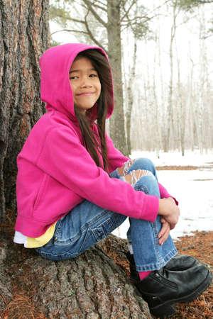 scandinavian girl: Child sitting under tree in winter