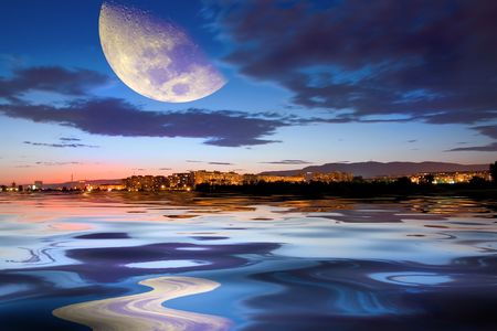 Town at sunset with moon and reflection Stock Photo