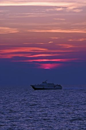 Boat at sunset sailing under sun Stock Photo - 652140