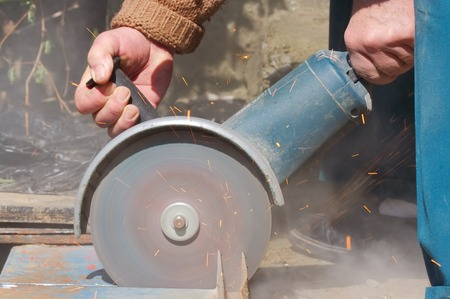 cutting through: Cutting through metal using power tool Stock Photo