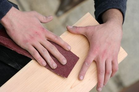 Carpenter is making wanted shapes of wooden plank