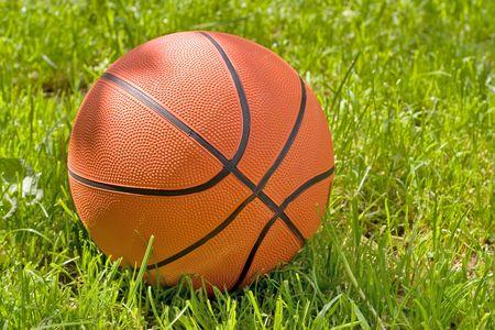 Orange basketball on green grass
