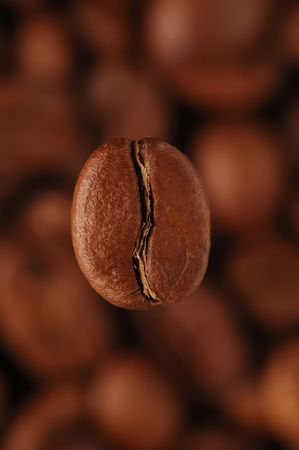 cheerfully: coffee-bean above coffee grains, vertical Stock Photo