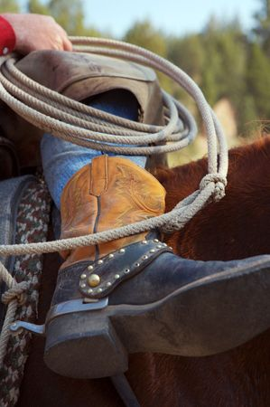 Shot of a cowboys boots and rope while on his horse