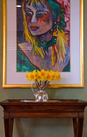 Interior Design Bright Painting with daffodills in a silver vase sitting on a side table