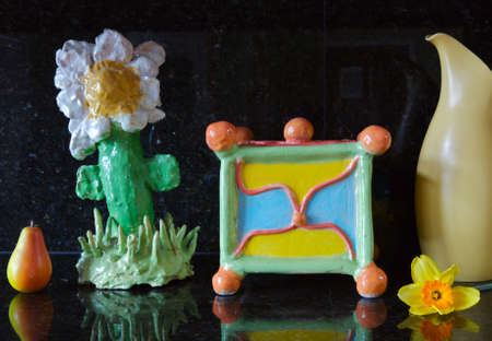 still-life of a hand built art objects made by a child with a pear, piece of pottery and a daffodill
