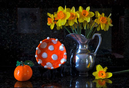 Artistic still-life of a pewter pitcher filled with daffodills a hand made orange with white polka-dotted bowl and a orange Stock Photo