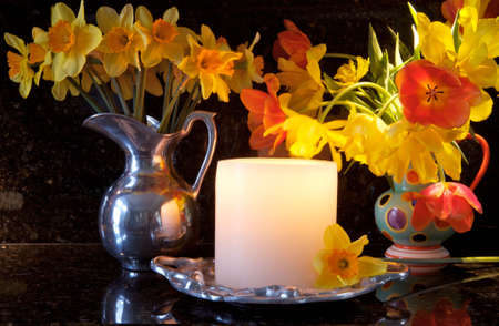 Beautiful pewter vase full of daffodills and vase of orange and yellow tulips, with a lit, glowing candle all on a black granite background Stock Photo