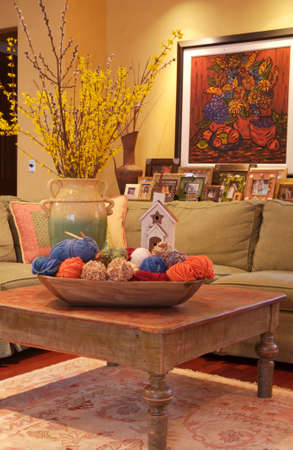 home decorating: Colorful Great Room nterior of a great room with a green sectional with a antique red wooden coffee table with a rustic white churchand vase of olive branches , big wooden bow full of yarn and a beautiful painting on the wall