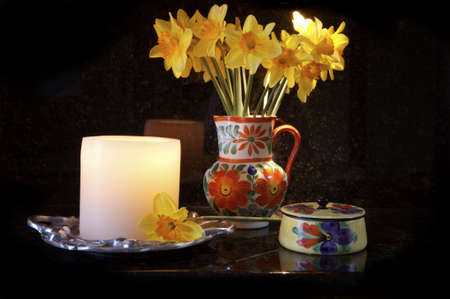 Pitcher with Dafodils and a lit Candle