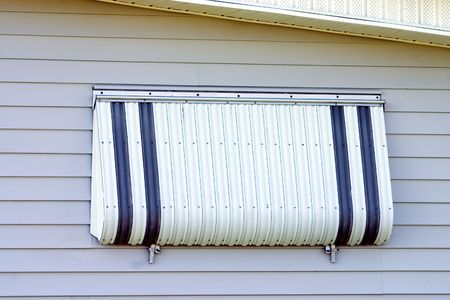 Hurricane protection aluminum shutter installed on tropical home Stock Photo