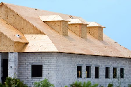 sheeting: New building under construction showing plywood roof sheeting and three dormers