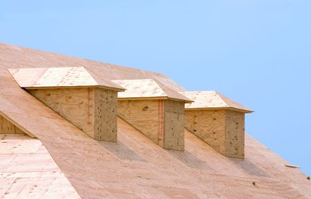 sheathing: New building under construction showing plywood roof sheeting and three dormers