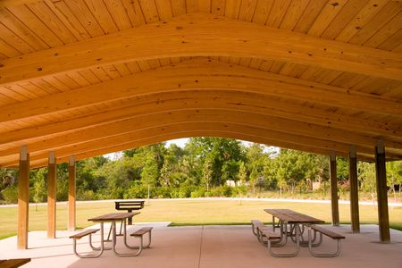 Picnic tables and grill under wood roof structure Stock Photo