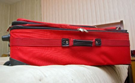 Wide angle shot of suit case on bed