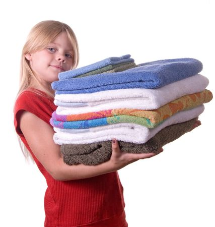Young girl helping with laundry carrying towels