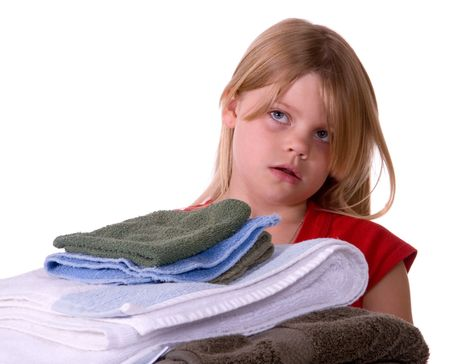 disgusted: Unhappy, disgusted young girl helping with laundry carrying towels Stock Photo