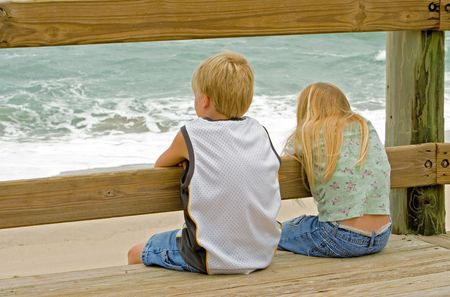 Young boy and girl (brother and sister) watching the ocean waves from the boardwalk