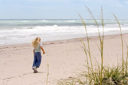 Young girl walking on the beach with Sea Oats in foreground