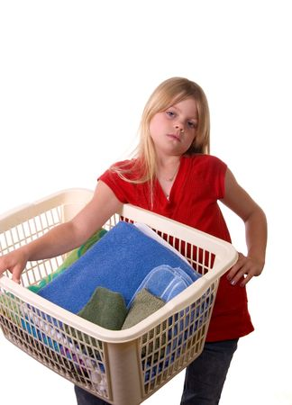 overly: Young girl helping with laundry carrying basket of towels but not overly happy about it
