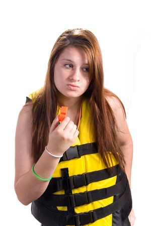 lifejacket: Attractive teen girl wearing ski vestlife jacket with a orange safety whistle in hand shot over white