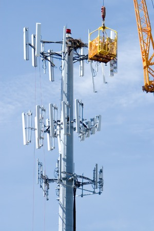 Cell phone company upgrading a communications tower Stock Photo