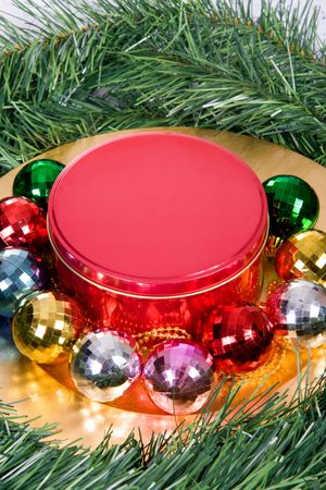Candy tin on gold platter surrounded by Christmas decorations photo