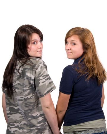 looking over shoulder: Two teenage girls side by side looking back over shoulder shot in studio over white background Stock Photo