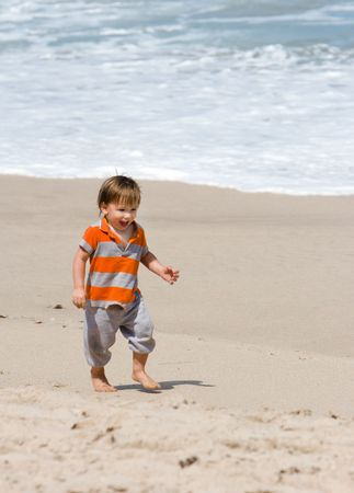 Young happy boy walking on sandy beach Stock Photo - 3003728