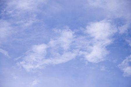 Wispy white clouds on blue sky background