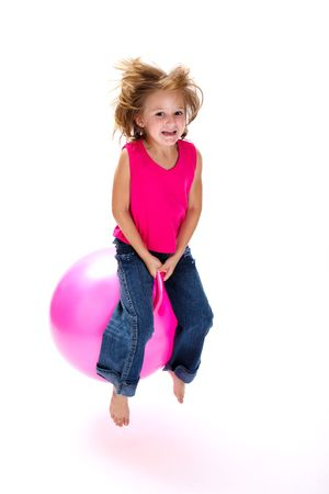 Young laughing girl bouncing on a pink space hopper Stock Photo