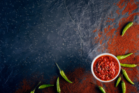 chilli sauce: Chilli and garlic relish on black slate background from above