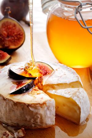 tabla de quesos: Queso Brie y figuras en rodajas vertieron con la miel en tabla de quesos de madera