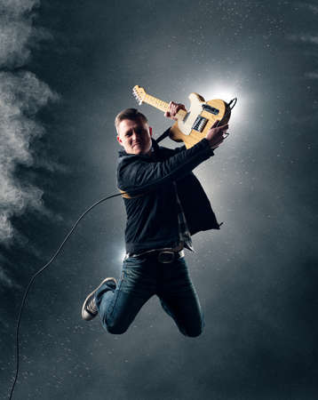concierto de rock: Rock and Roll Guitarrista que salta con la guitarra eléctrica con el humo y el polvo en el fondo