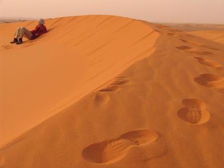desert footprint: Man siting on a desert dune at sunset