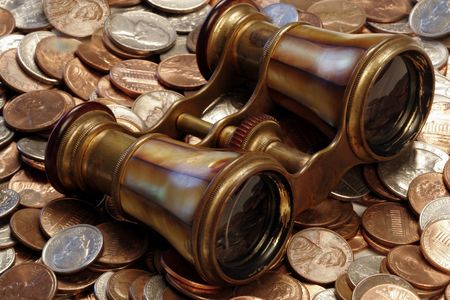 timing the market: An old brass set of opera glasses atop US coins portrays the search for financial clarity Stock Photo