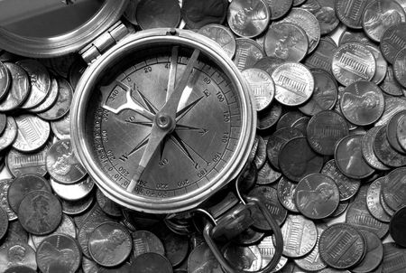 atop: A black and white image of a brass compass atop US coins. This pairing portrays navigating financial waters