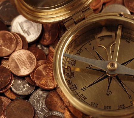 pulling money: An old brass compass atop US coins portrays business timing and navigation of business decisions.